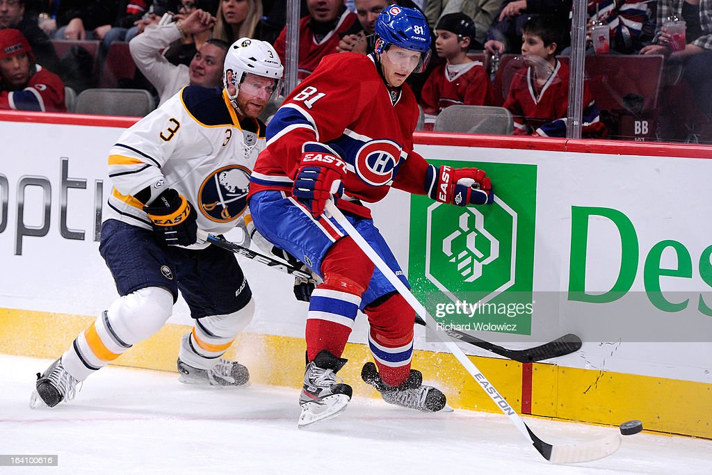 Lars Eller #81 of the Montreal Canadiens and Jordan Leopold #3 of the Buffalo Sabres chase the puck into the corner during the NHL game at the Bell Centre on March 19, 2013 in Montreal, Quebec, Canada.