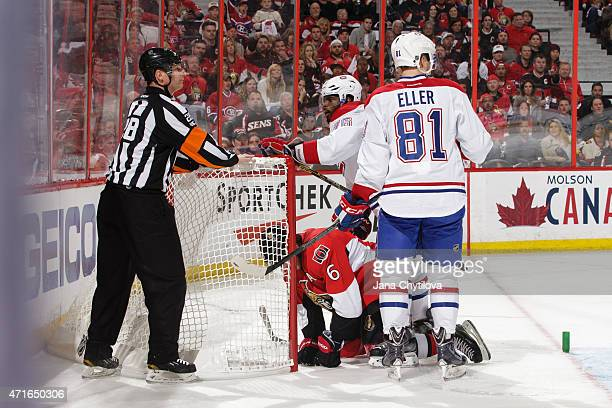 Lars Eller of the Montreal Canadiens and referee Chris Lee look on as Bobby Ryan of the Ottawa Senators kneels on the ice after being knocked down by...