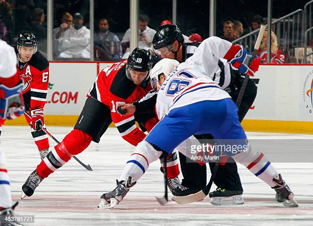 Lars Eller of the Montreal Canadiens and Travis Zajac of the New Jersey Devils face off during the game at the Prudential Center on December 4 2013...