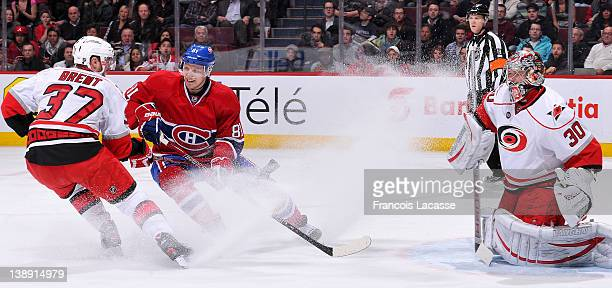Lars Eller of the Montreal Canadiens battles for position with Tim Brent in front of goalie Cam Ward of the Carolina Hurricanes during the NHL game...