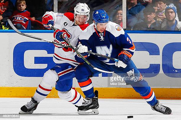 Lars Eller of the Montreal Canadiens battles for the puck with Travis Hamonic of the New York Islanders at Nassau Veterans Memorial Coliseum on...