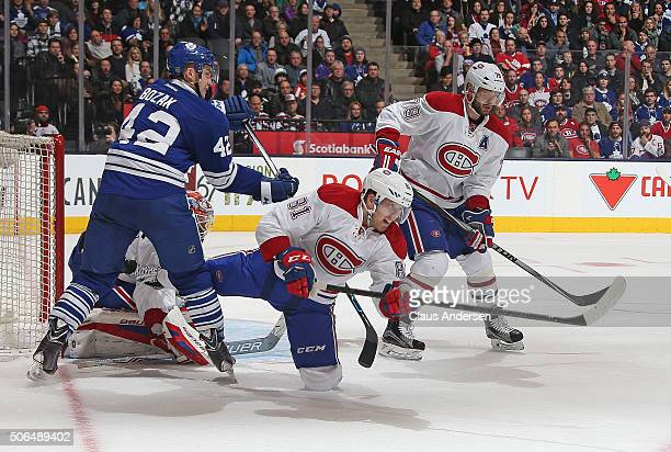 Lars Eller of the Montreal Canadiens clears a puck against Tyler Bozak of the Toronto Maple Leafs during an NHL game at the Air Canada Centre on...
