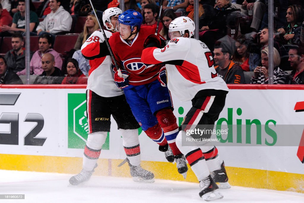 <a gi-track='captionPersonalityLinkClicked' href=/galleries/search?phrase=Lars+Eller&family=editorial&specificpeople=4324947 ng-click='$event.stopPropagation()'>Lars Eller</a> #81 of the Montreal Canadiens is checked by Michael Sdao #58 and <a gi-track='captionPersonalityLinkClicked' href=/galleries/search?phrase=Cody+Ceci&family=editorial&specificpeople=7324783 ng-click='$event.stopPropagation()'>Cody Ceci</a> #5 of the Ottawa Senators during an NHL preseason game at the Bell Centre on September 26, 2013 in Montreal, Quebec, Canada.