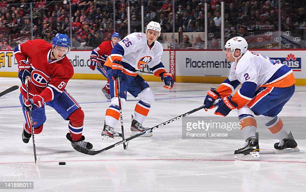 Lars Eller of the Montreal Canadiens skates in on Nino Niederreiter and defenceman Mark Streit of the New York Islanders during the NHL game on March...