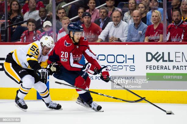 Lars Eller of the Washington Capitals controls the puck against Jake Guentzel of the Pittsburgh Penguins in the first period at Capital One Arena on...