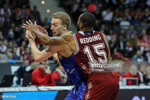 Lars Lagerpusch of Braunschweig Reggie Redding of Bayern Muenchen battle for the ball during the easyCredit BBL Basketball Bundesliga match between...