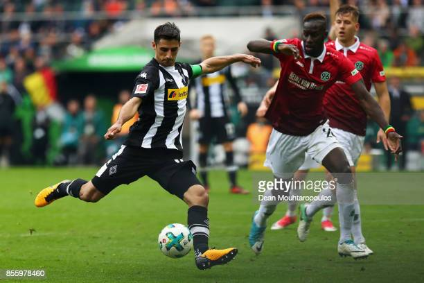 Lars Stindl Borussia Monchengladbach shoots on goal in front of Kenan Karaman of Hannover 96 during the Bundesliga match between Borussia...