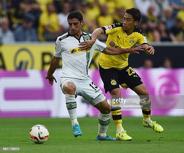 Lars Stindl of Borussia Moenchengladbach and Shinji Kagawa of Borussia Dortmund battle for the ball during the Bundesliga match between Borussia...