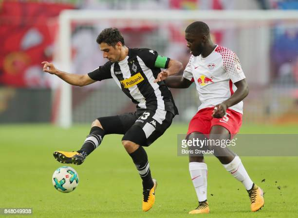 Lars Stindl of Borussia Moenchengladbach is challenged by Dayot Upamecano of RB Leipzig during the Bundesliga match between RB Leipzig and Borussia...