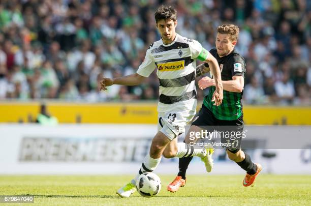 Lars Stindl of Borussia Moenchengladbach is chased by Daniel Baier of FC Augsburg during the Bundesliga Match between Borussia Moenchengladbach and...