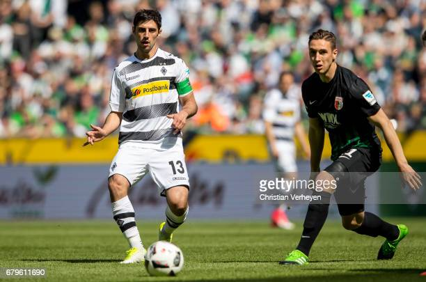 Lars Stindl of Borussia Moenchengladbach is chased by Dominik Kohr of FC Augsburg during the Bundesliga Match between Borussia Moenchengladbach and...