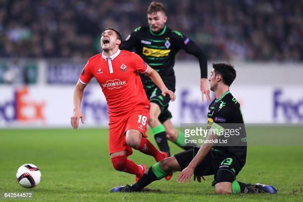 Lars Stindl of Borussia Moenchengladbach tackles Sebastian Cristoforo of ACF Fiorentina during the UEFA Europa League Round of 32 first leg match...