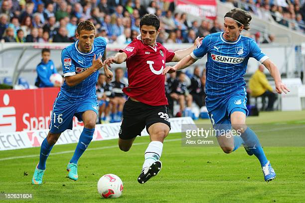 Lars Stindl of Hannover is challenged by Sebastian Rudy and Fabian Johnson of Hoffenheim during the Bundesliga match between 1899 Hoffenheim and...