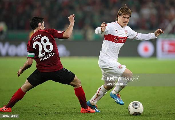 Lars Stindl of Hanover challenges Gotoku Sakai of Stuttgart during the Bundesliga match between Hannover 96 and VfB Stuttgart at HDIArena on April 25...