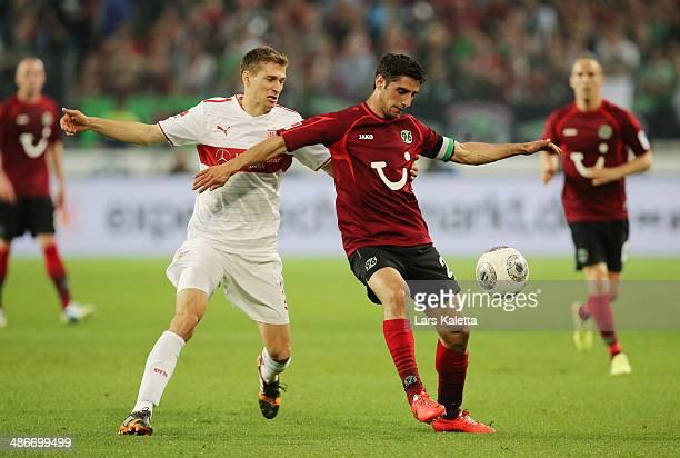 Lars Stindl of Hanover is challenged by Daniel Schwab of Stuttgart during the Bundesliga match between Hannover 96 and VfB Stuttgart at HDIArena on...