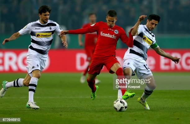 Lars Stindl of Moenchengladbach and Branimir Hrgota of Frankfurt battle for the ball during the DFB Cup semi final match between Borussia...