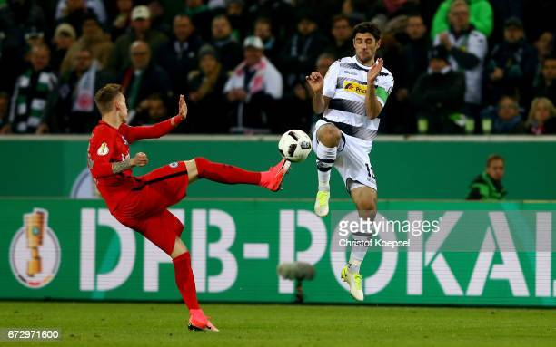 Lars Stindl of Moenchengladbach and Marius Wolf of Frankfurt battle for the ball during the DFB Cup semi final match between Borussia...