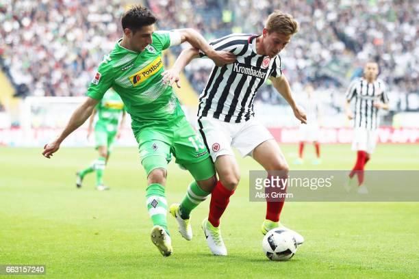 Lars Stindl of Moenchengladbach is challenged by Bastian Oczipka of Frankfurt during the Bundesliga match between Eintracht Frankfurt and Borussia...