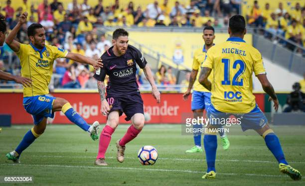 Las Palmas' Brazilian defender Michel Macero Rocha and Las Palmas' misfielder Montoro vie with Barcelona's Argentinian forward Lionel Messi during...