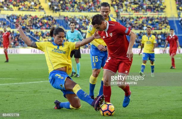 Las Palmas' Uruguayan defender Mauricio Lemos tackles Sevilla's French forward Wissam Ben Yedder beside Las Palmas' midfielder Roque Mesa Quevedo...