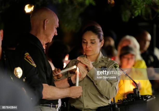 Las Vegas Metropolitan Police Department Capt Sasha Larkin lights a candle during during a prayer vigil held at Mountain Crest Park for the victims...