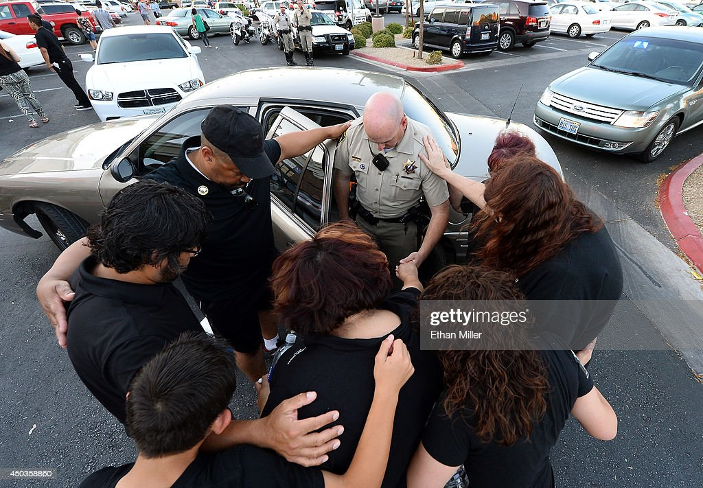 Las Vegas Metropolitan Police Department Detective Mike Souder (C) prays with attendees at a vigil outside CiCi's Pizza on June 9, 2014 in Las Vegas, Nevada. The Las Vegas Metropolitan Police Department says officers Alyn Beck and Igor Soldo were shot and killed yesterday at the restaurant by Jerad Miller and his wife Amanda Miller. Police say the Millers then went into a nearby Wal-Mart where Amanda Miller killed Joseph Wilcox before the Millers killed themselves.