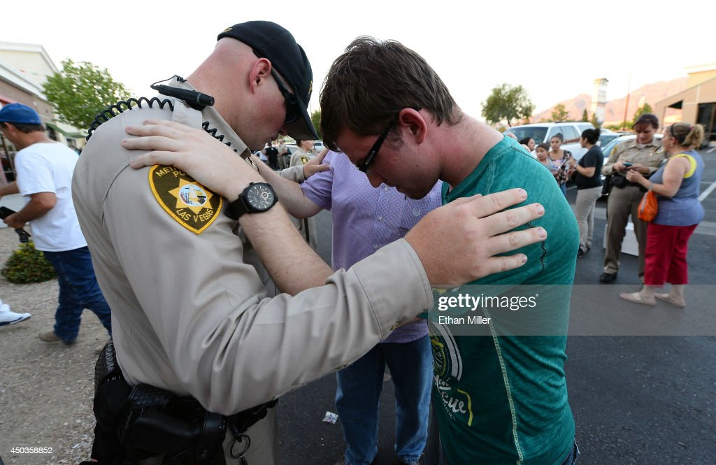 Las Vegas Metropolitan Police Department Officer Harrison Porter (L) prays with Ryan Rasmussen of Nevada during a vigil outside CiCi's Pizza on June 9, 2014 in Las Vegas, Nevada. The Las Vegas Metropolitan Police Department says officers Alyn Beck and Igor Soldo were shot and killed yesterday at the restaurant by Jerad Miller and his wife Amanda Miller. Police say the Millers then went into a nearby Wal-Mart where Amanda Miller killed Joseph Wilcox before the Millers killed themselves.