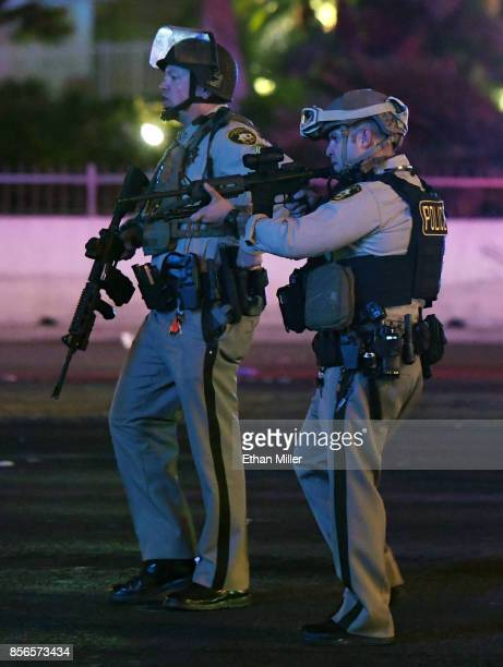 Las Vegas Metropolitan Police Department officers point their weapons at a car driving down closed Tropicana Ave near Las Vegas Boulevard after a...