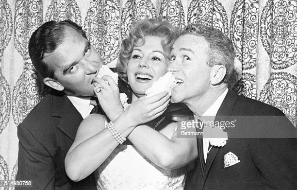 A vivacious Eva Gabor 33yearold actress feeds her wedding cake to her new husband Richard Brown New York textile executive left and comedian Red...
