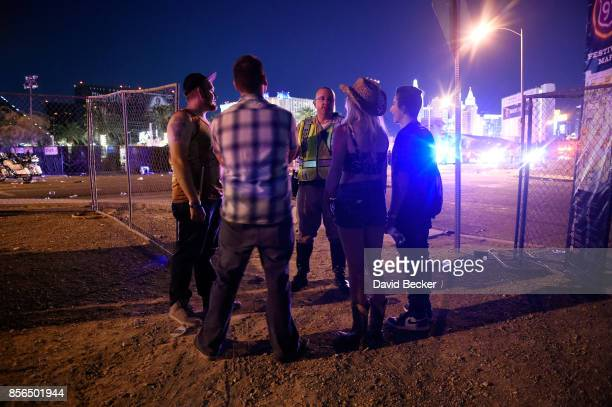 Las Vegas police officer informs people to stay in place after shots were fired near Route 91 Harvest Country Music Festival on October 1 2017 in Las...