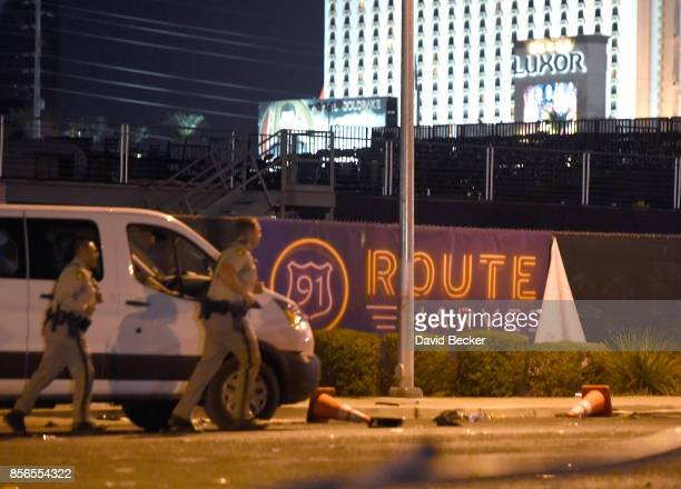 Las Vegas police run by a banner on the fence at the Route 91 Harvest country music festival grounds after a active shooter was reported on October 2...