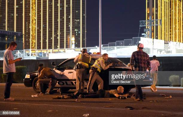 Las Vegas police stand guard along the streets outside the the Route 91 Harvest country music festival grounds after a active shooter was reported on...