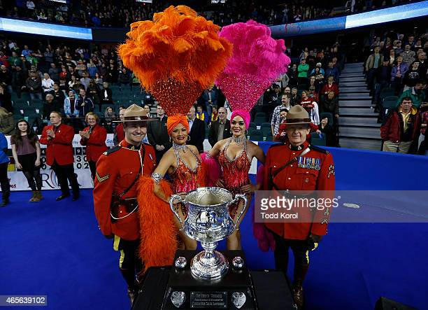 Las Vegas show girls pose with members of the Royal Canadian Mounted Police and the Tankard trophy at the gold medal game in curling during the Tim...