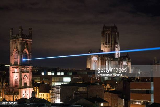 A laser beam illuminates the sky as businesses in Liverpool switch on their Christmas lights and window displays in the hope of an early boost to...