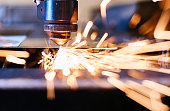 CNC Laser cutting of metal with sparks, modern industrial technology. Small depth of field.