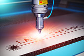 Laser cutting metal industry concept: macro view of industrial digital CNC - computer numerical control CO2 invisible laser beam cutter machine cutting stainless steel sheet with lot of bright shiny s