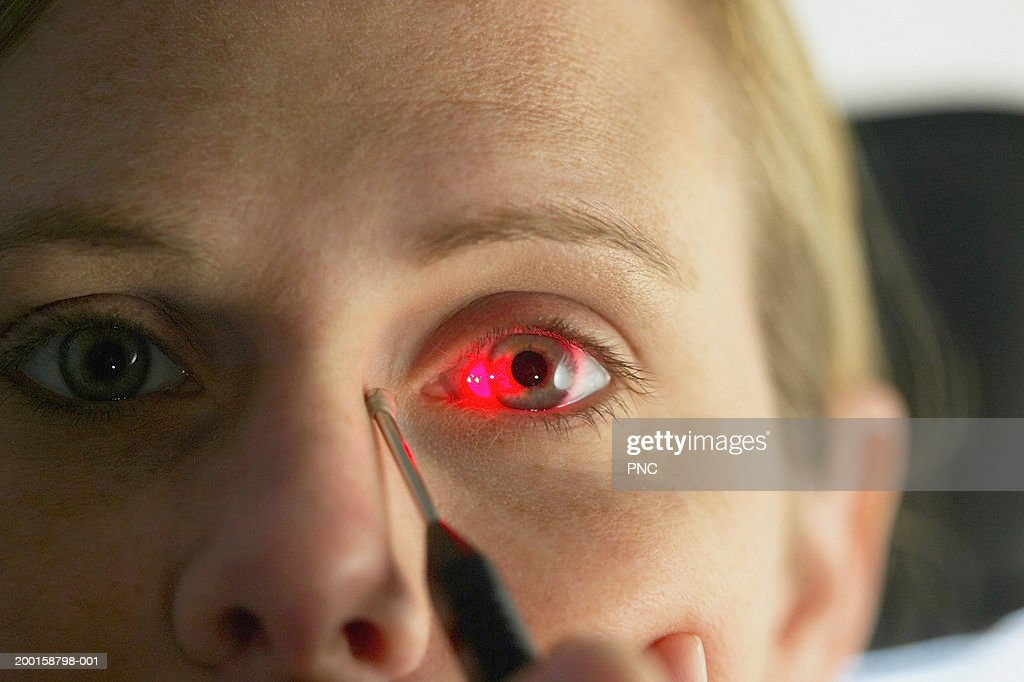 Laser shining on woman's eye during eye exam, close-up (focus on eye)