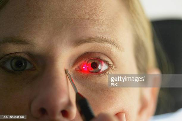 Laser shining on woman's eye during eye exam, close-up (focus on eye)
