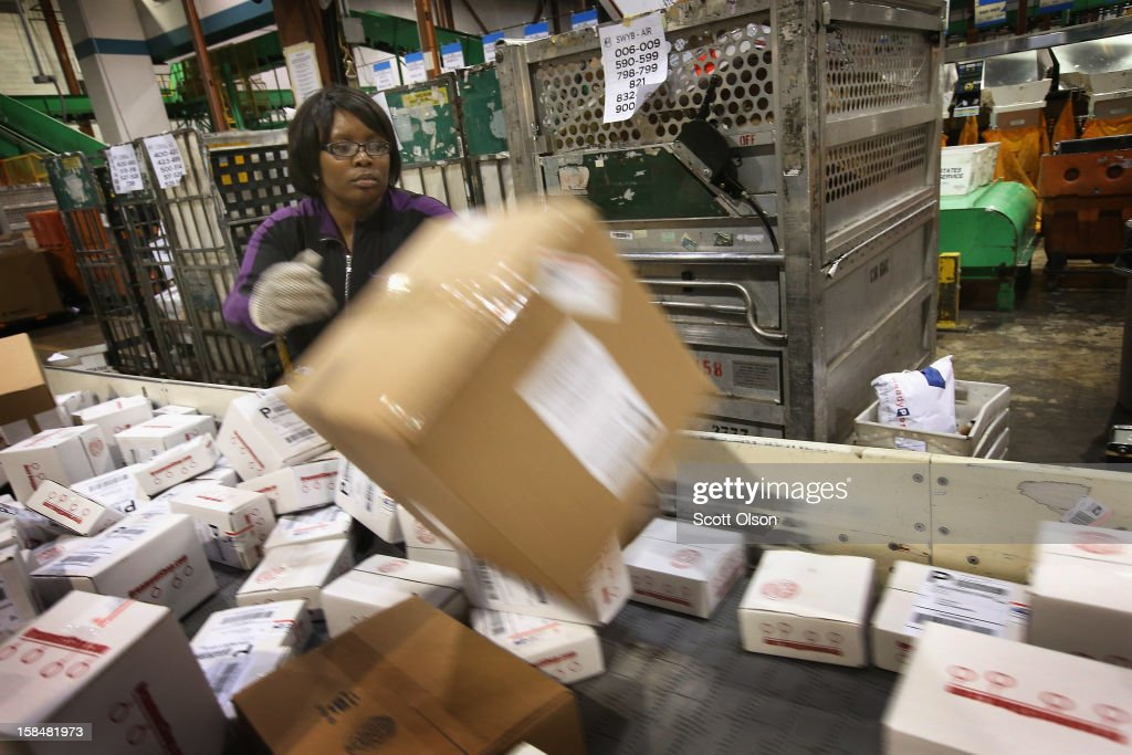 Lashaun Kerby loads mail onto a conveyor at the United States Postal Service (USPS) Chicago Logistics and Distribution Center on December 17, 2012 in Elk Grove Village, Illinois. Today is busiest day of the year for the USPS. They expect to move 658 million pieces of mail nationwide, 320 thousand from this facility.