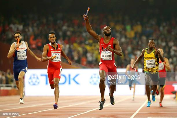 Lashawn Merritt of the United States crosses the line to win gold ahead of Martyn Rooney of Great Britain Machel Cedenio of Trinidad and Tobago and...