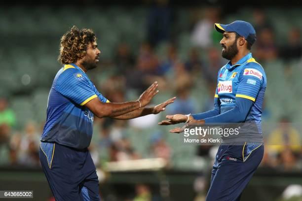 Lasith Malinga and Chamara Kapugedera of Sri Lanka celebrate after Kapugedera took a catch to get the wicket of Travis Head of Australia during the...
