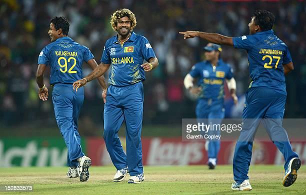 Lasith Malinga of Sri Lanka celebrates with Nuwan Kulasekara and Mahela Jayawardene after winning the super over and beating New Zealand during the...