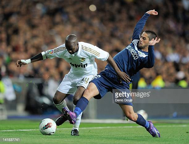 Lass Diarra of Real Madrid competes for the ball with Isco of Malaga during the La Liga match between Real Madrid CF and Malaga CF at Estadio...