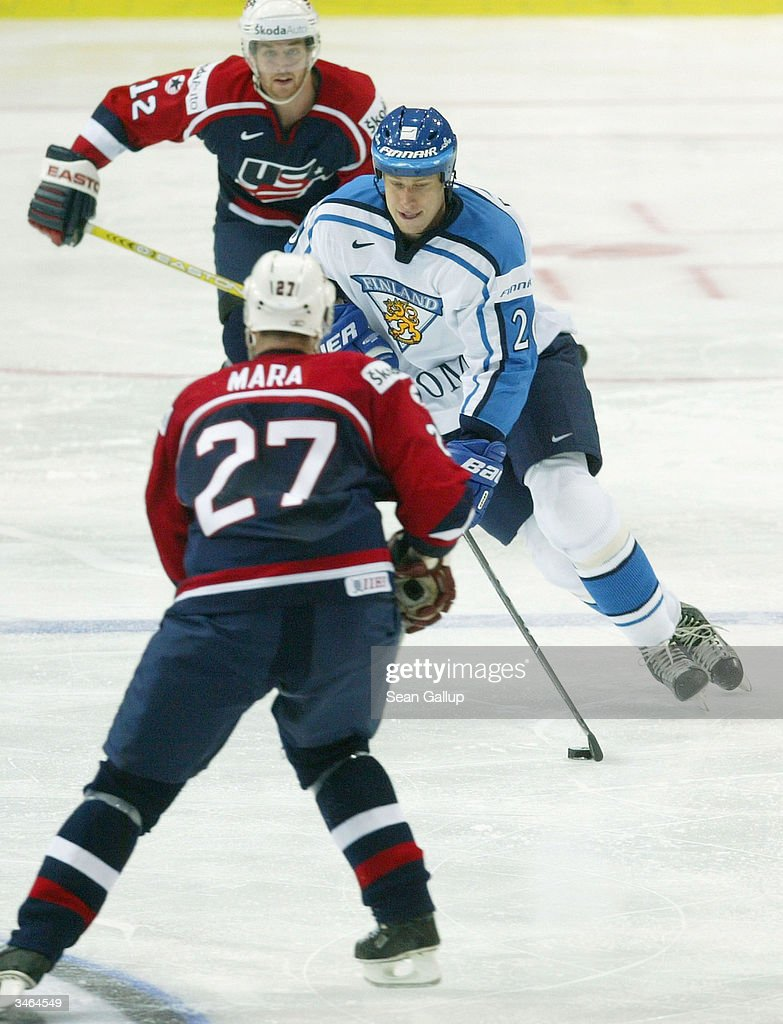 Lasse Pirjeta of Finland pushes the puck past Paul Mara and Ryan Malone of the USA in the teams' Group B qualifying match at the International Ice...