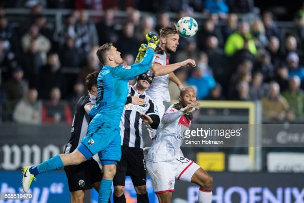Lasse Sobiech of St Pauli is tackled by goalkeeper Marcel Schuhen of Sandhausen during the Second Bundesliga match between SV Sandhausen and FC St...