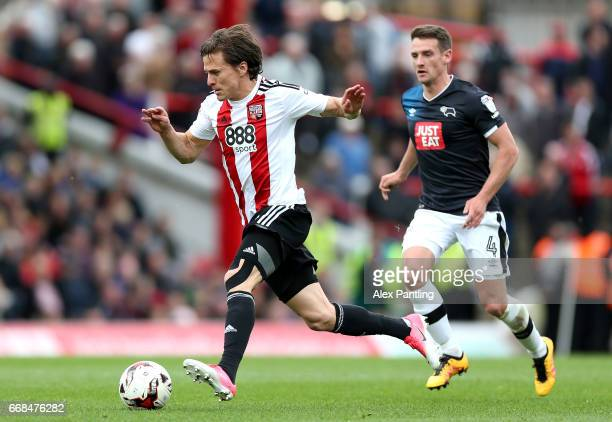 Lasse Vibe of Brentford is chased by Craig Bryson of Derby County during the Sky Bet Championship match between Brentford and Derby County at Griffin...