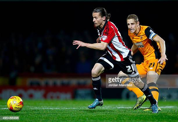 Lasse Vibe of Brentford takes the ball past Michael Dawson of Hull during the Sky Bet Championship match between Brentford and Hull City on November...