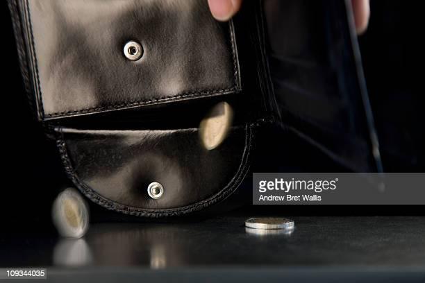 last few coins falling from an empty wallet