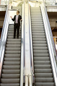 Man standing on an escalator with a flipchart, ready for his business presentation