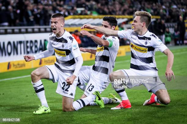 Laszlo Benes of Gladbach celebrates with Lars Stindl and Patrick Herrmann after he scores the opening goal during the Bundesliga match between...
